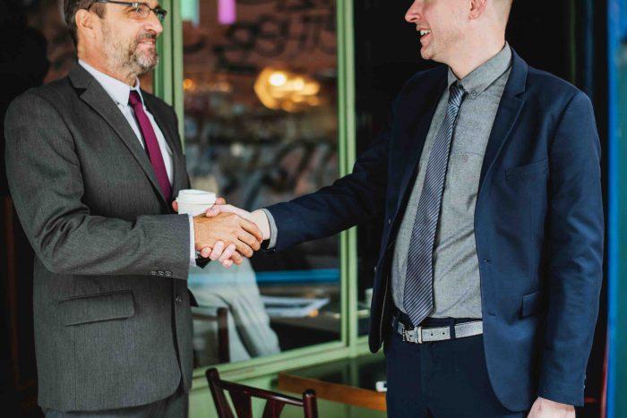 En la imagen se aprecian dos personas estrechándose las manos, un comportamiento clave para el Rapport en PNL